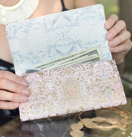 "A woman's hands are seen holding the ""Lotus Garden"" wallet with cash sticking out of it."