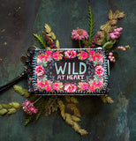 "The Wristlet ""Gypsy Rose"" Wallet lies on the bluish floor of pinkish wild flowers."