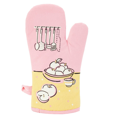 The pink oven mitt has pictures of kitchen utensils, a bunch of apples, and teacup on a yellow table.