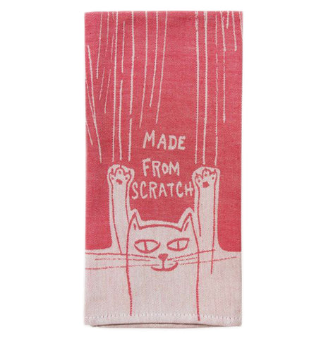 "This red cotton towel has a design of white lines at the top, and a cat at the bottom. The stretching cat is shown in red lines against a white background. Above the cat are the words, ""Made From Scratch""."