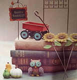 The (Mini) Harvest Sign with Hook sits on top of the stack of books along with a red mini waggon, a mini owl sits in front of the books along with three different gourds to its left, while three sunflower picks are leaning on the books on its right.