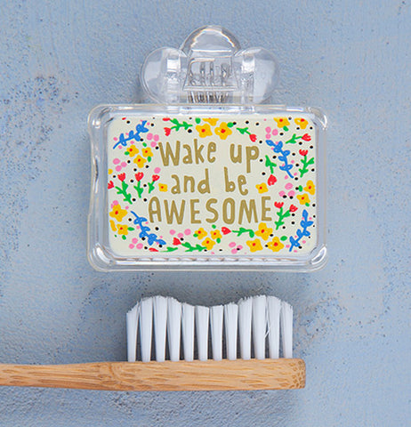 Clear plastic toothbrush cover with a white label with a red, blue, green, yellow, and pink design on the front with gold letters that read Wake Up and be Awesome next to a tan and white toothbrush on a blue background.