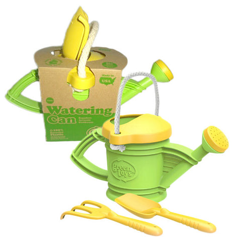 These green and yellow toy watering cans are shown with a yellow plastic rake and shovel. The watering can near the top of the image is shown in its cardboard packaging.