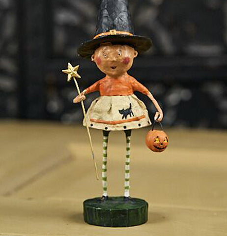 The witch figurine is shown sitting on a wooden table in front of a black wall.
