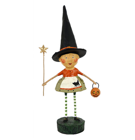 This witch figurine wears her pointed hat and holds a star-shaped wand in one hand and a pumpkin-shaped basket in the other. She wears an orange shirt and a green skirt.
