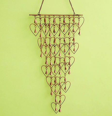 Shimmering Bells with Hearts wind chime over a green background with bells inside hearts.