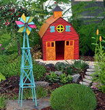 The miniature windmill is shown in front of the mini barn within a small fairy garden.