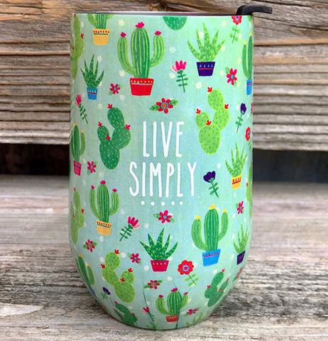 "The insulated cyan green tumbler has cacti pattern with words ""Live Simply"" with wooden background"