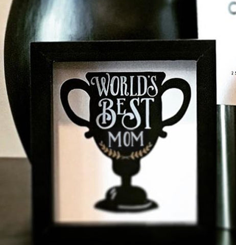 "The ""World's Best Mom"" Box Sign sits against the black vase."