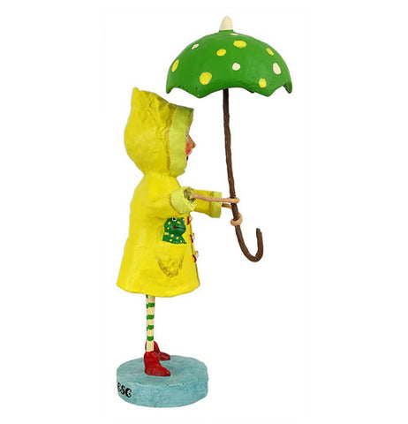 The girl figurine dressed in the yellow raincoat and holding the umbrella is shown from a side angle.