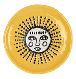 This ceramic yellow coaster has a white sun with a face