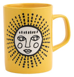 Yellow ceramic mug with a white decorative sun with a face