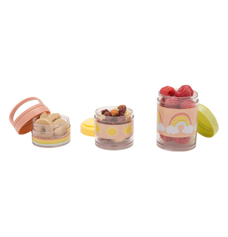 Three snack containers are seen side by side. The container on the left a pastel pink lid tilted slightly off it, has a rainbow bottom, and has crackers inside of it. The one in the middle has a pastel yellow design in the middle, with raisins inside of it, and a yellow lid behind it. The right one has raspberries inside of it, a pastel green lid leaning on it, and a rainbow design on it with a pastel pink background.