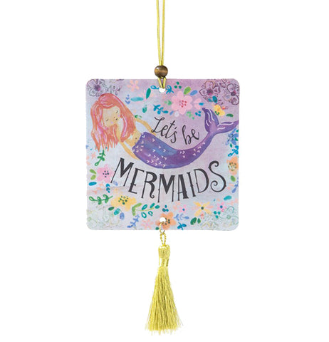 "This square air freshener has a design of a mermaid with a purple fish tail swimming around some yellow and pink flowers. The words, ""Let's Be Mermaids"" are shown in black lettering above and below the mermaid."