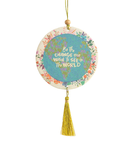 "This Air Freshener has a Floral Globe Design that says ""Be The Change You Wish To See In The World"". It is hanging up and has a sash hanging down."
