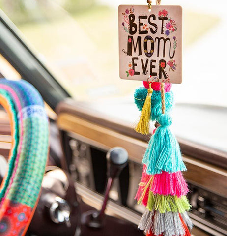 "The ""Best Mom Ever"" air freshener is shown hanging from a car's rear view mirror along with some different colored tassels."