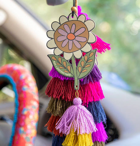 "Flower shaped air freshener with sentiment that reads ""Make a Difference Today"" in white words hanging from a rearview mirror with pink and orange tassels hanging down. There are a stack of different colored tassels hanging behind the air freshener."