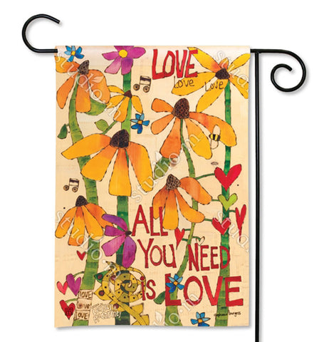 "This orange polyester garden flag with a green, orange, red, purple, and yellow flower design has musical notes that say, ""All You Need is Love"" in red lettering. It is held up by a large black metal hook."