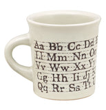 This white ceramic mug has a design of the alphabet all around it.