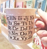 "The Cuppa This Cuppa ""Alphabet"" Mug is being held by a human hand."