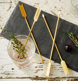The golden arrow-shaped stir sticks are shown in criss-cross pattern next to a drink on a black table cloth.