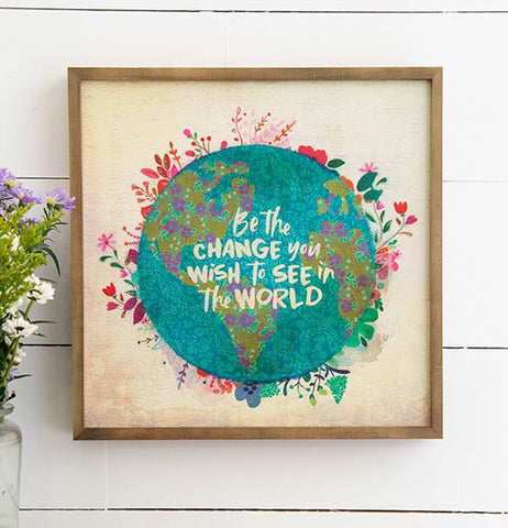 "The ""Be the Change"" Bungalow Art hangs on the wall with a vase of flowers."