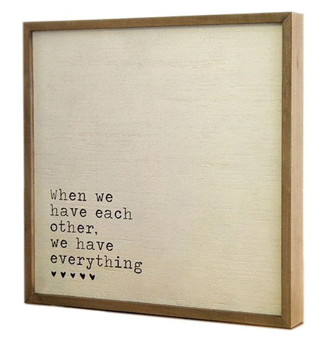 "This cream colored sign with a wooden frame displays the words, ""When We Have Each Other, We Have Everything"" in black lettering with five small heart symbols in the lower left hand corner."