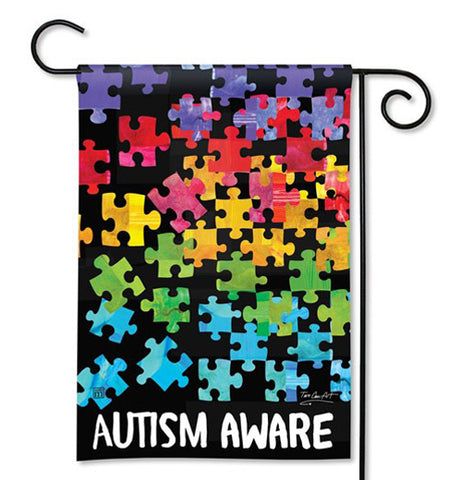 "This garden flag says, ""Autism Awareness"" in white lettering at the bottom of the flag. Rainbow colored puzzle shaped pieces adorn the space above the words. The flag is shown hanging on a black metal bar."