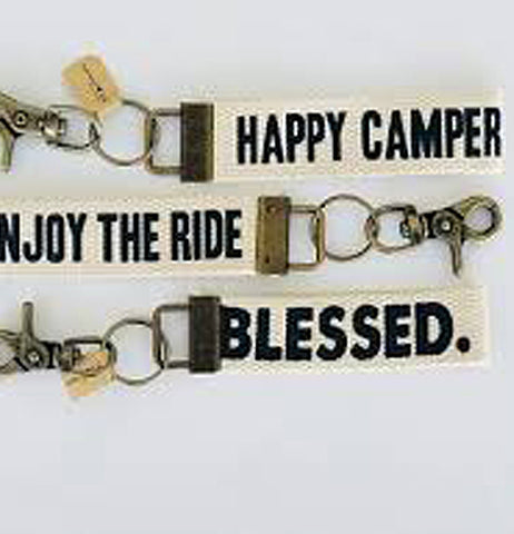 "The key fob saying, ""Enjoy the Ride"" is shown sitting in the middle between two key fobs saying, ""Happy Camper"" and ""Blessed""."