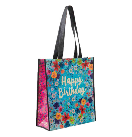 "This blue shopping bag with pink sides and black handles is covered with a design of red, blue, green, and yellow flowers. The words, ""Happy Birthday"" sit in the middle of the bag in white lettering."