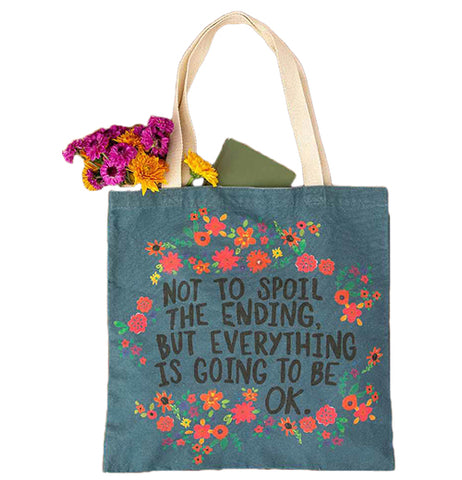 "This blue bag with white handles has a design of red, orange, and hot pink flowers surrounding the phrase, ""Not to Spoil The Ending, But Everything is Going to be Ok."" in black lettering."