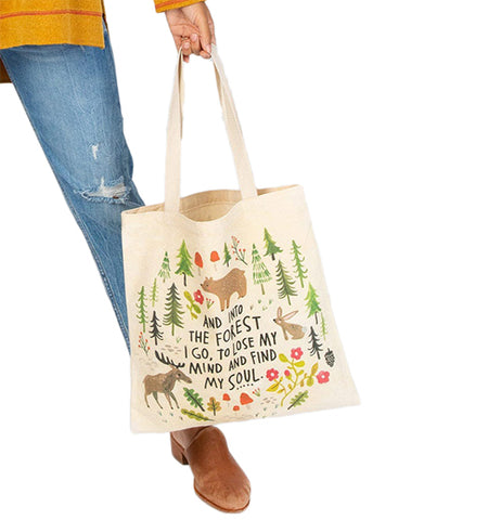 A woman in blue jeans and a yellow shirt is shown holding the white bag with the forest design.