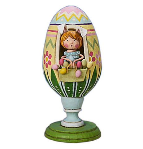 This colorful figurine has a girl in bunny ears wearing a blue dress and sitting in a large yellow, green, blue and pink Easter egg with red and pink flowers on a green pedestal.