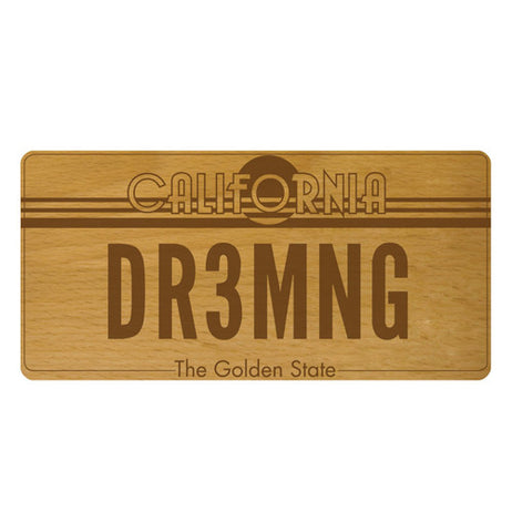 "A beechwood cheese board that says ""DR3MNG"" on it."