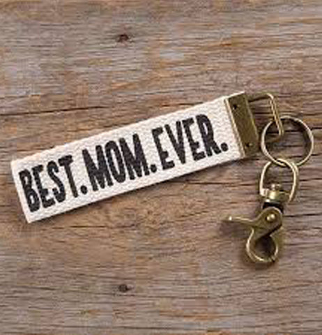 a white key fob that says' Best Mom Ever' with a metal clip sitting on wood paneling.