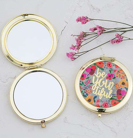 "Two compacts, one opened compact mirror with pink flowers above the closed one with a message ""BeYoutiful"""
