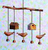 Brown, red, and yellow bird and birdhouse steel wind chimes hanging up in front of a colored wall.