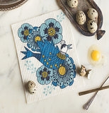 "The ""Birdland"" Dish Cloth on the marble countertop with speckled bird eggs with an egg broken."