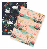 One pink notebook with palm trees, pink flowers and flamingos, and one black notebook with flowers and white swans.