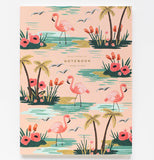 One pink notebook with palm trees, pink flowers and flamingos standing in turquoise water.