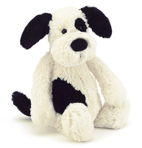 white puppy with black spots, and black ears and tail.