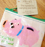 The Change is Good coin purse with pink piggy bank design laying on a table. Showing its tan tag