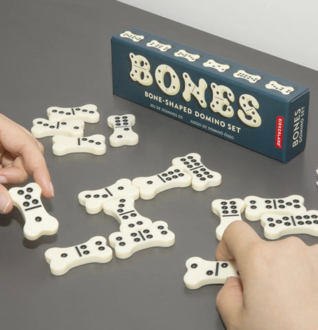The black box is shown with its bone shaped dominoes put in a set for a dominoes game.