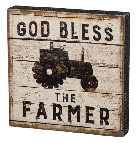 "This box sign has the words ""God Bless The Farmer"" with a tractor in the middle."