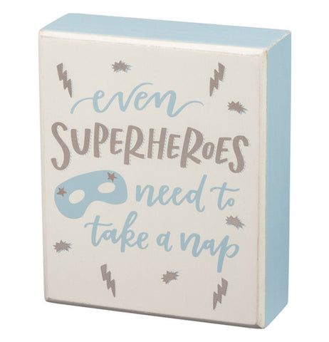 "This box sign says ""Even Superheroes Need To Take A Nap."" The sign is white, blue, and silver."