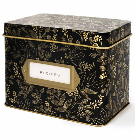"This black metal box is designed with golden botanical branches, floral and laurel leaves. The same design covers the lid. In the middle of the box is a white sign with a golden border, in back text the sign that reads, ""Recipes."""