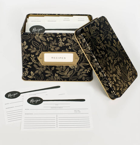The black metal box with a golden botanical branches, floral and laurel leaves design is shown with its lid off and recipe papers folded up inside it. Outside of the box are some blank recipe papers, the recipe papers are designed with a black spoon at the top of the page.