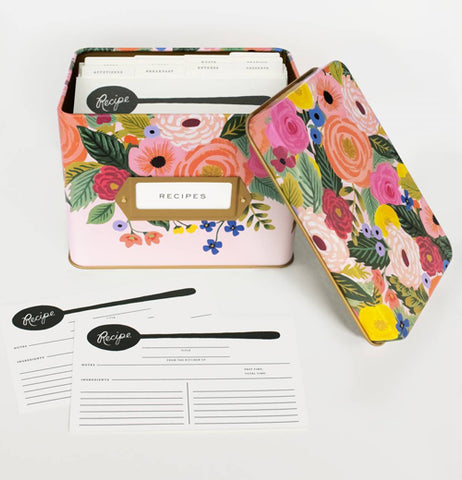 The pink metal box with the multi-colored rose design is shown with its lid off and recipe papers folded up inside it. Below the box are some blank recipe papers, with a black spoon design at the top of the card.