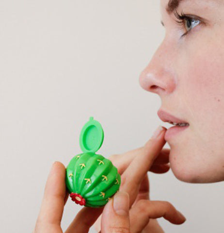 Women applying lip balm from a ball cactus shaped container.