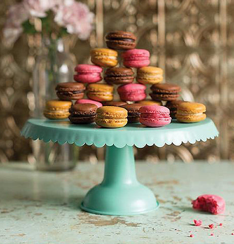 Aqua metal cake stand with a drape design with cupcakes displayed in a triangular design.